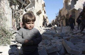 A child is seen amid the rubble of damaged buildings in Aleppo